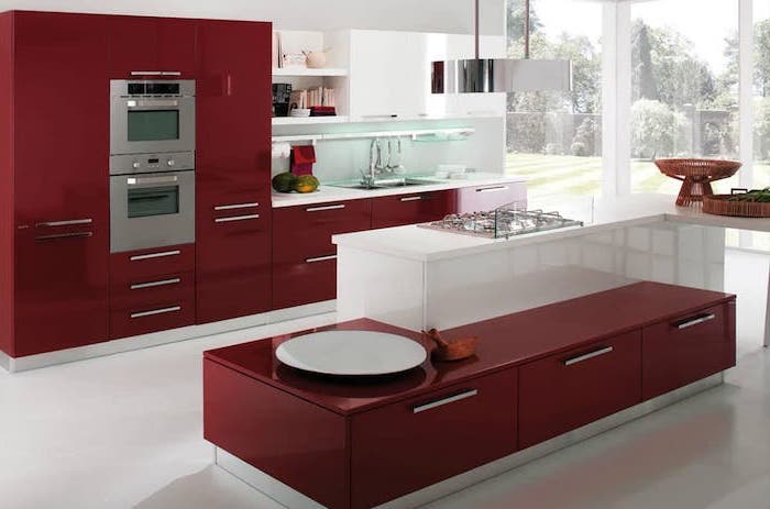 kitchen island with bar seating, red cabinets and drawers, white floor, large windows