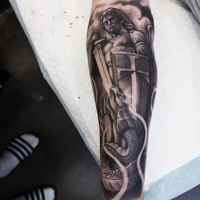 the archangel michael, slaying the snake, religious theme, tattoo ideas for men arm