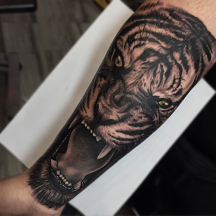 roaring lion, forearm tattoos, white paper, wooden floor