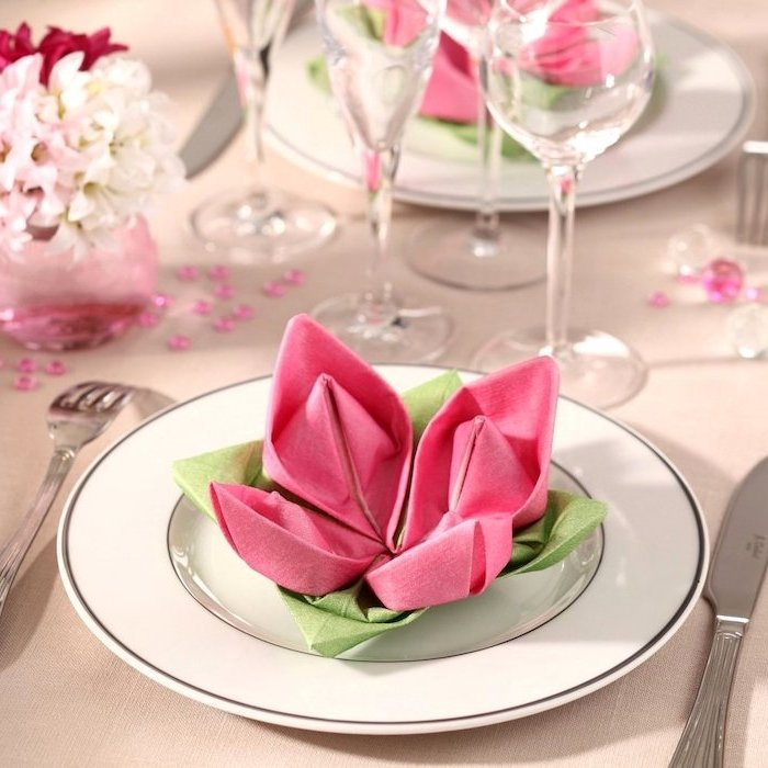 rose shaped, pink and green napkins, on a white plate, how to fold napkin fancy, small bouquet