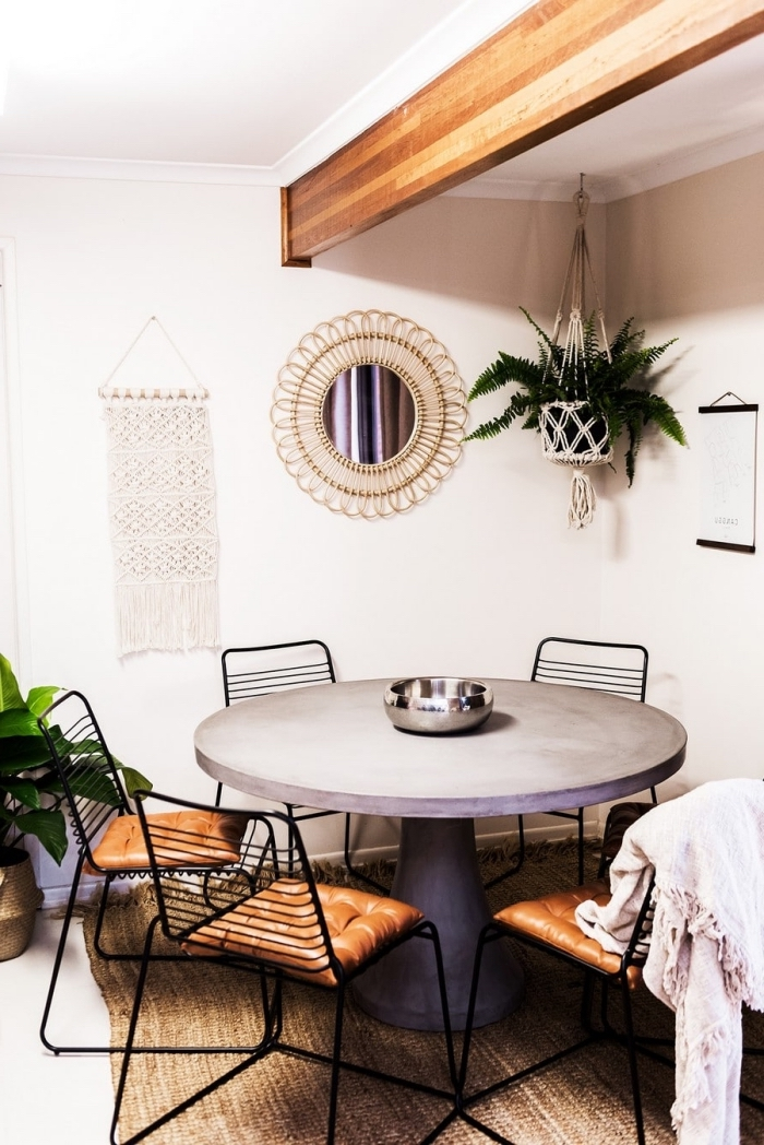 woven wall tapestry, round table, black metal chairs, leather cushions, white walls, potted plants