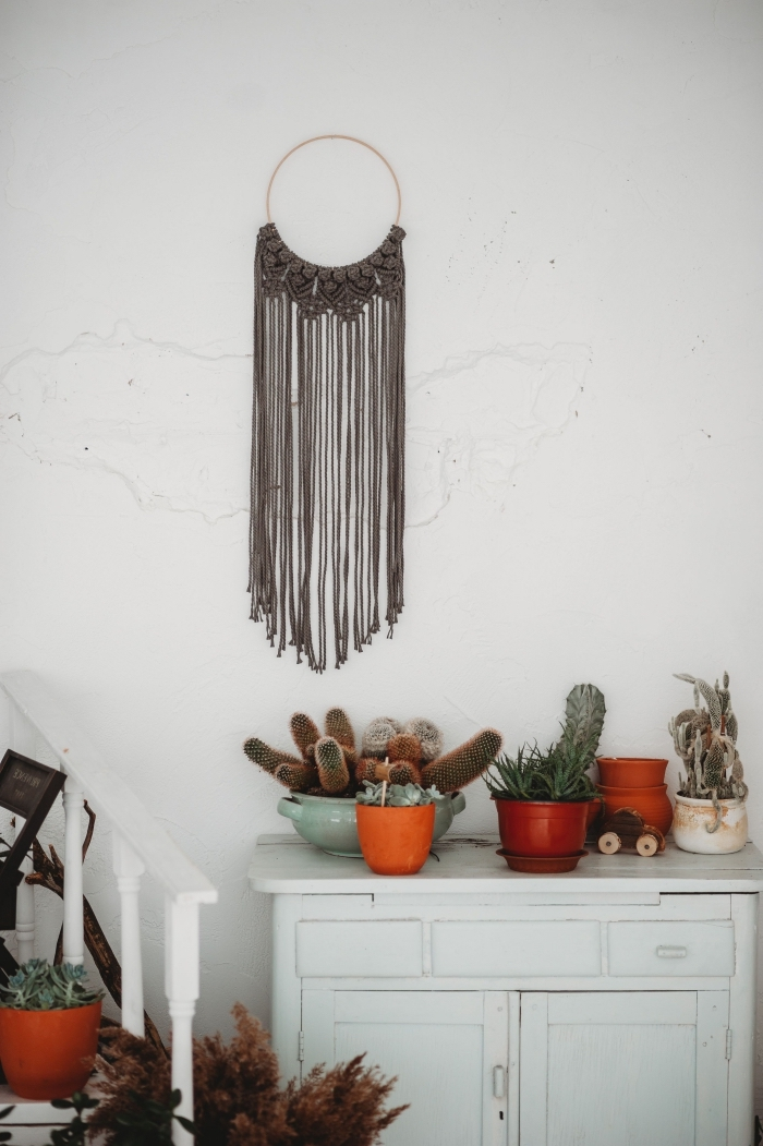 white walls, vintage cabinet, potted cactuses, woven wall tapestry, grey macrame