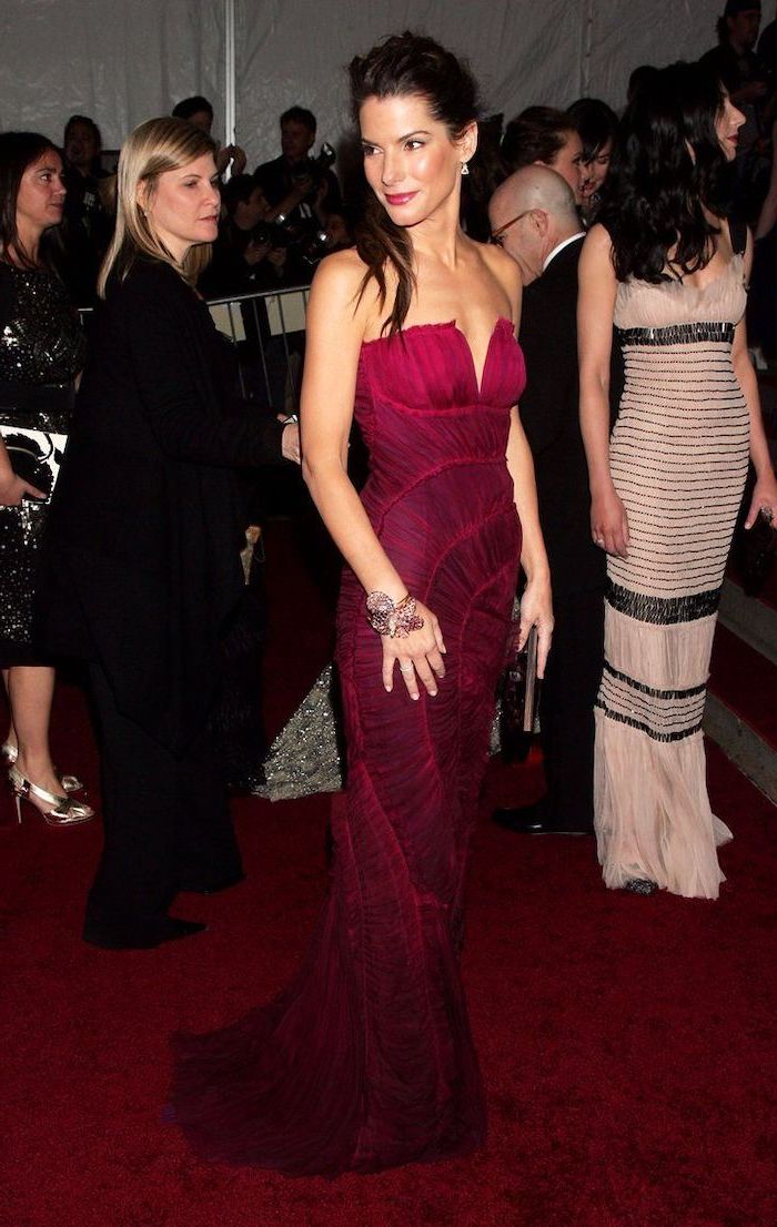 sandra bullock, fashion museum nyc, hot pink dress, strapless dress, large bracelet, brown hair, in a ponytail