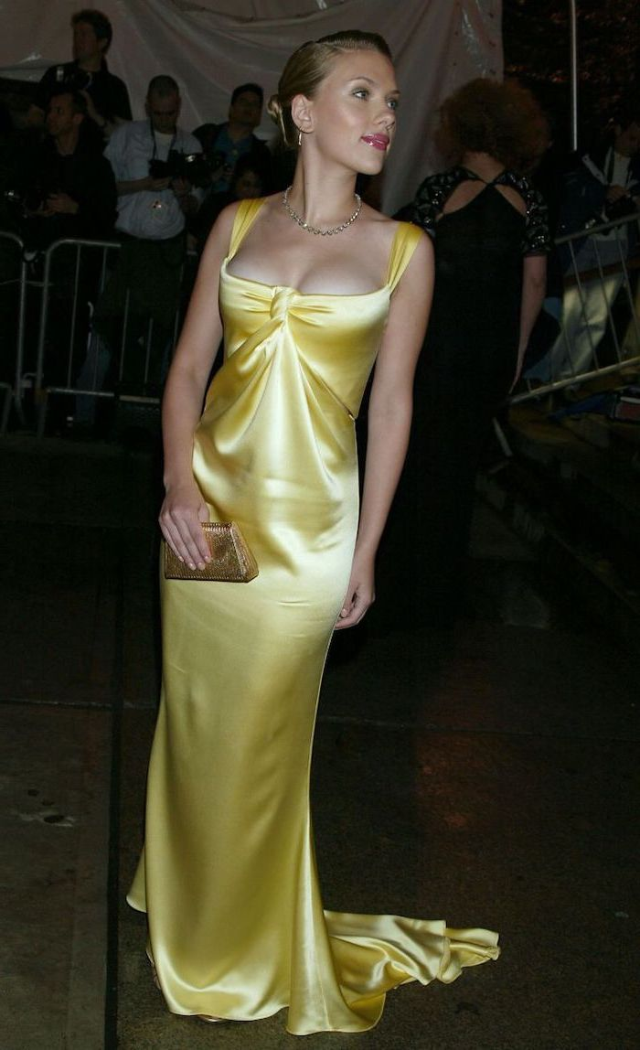 yellow satin dress, scarlett johannsson, fashion museum nyc, blonde hair, in a low updo, yellow clutch bag