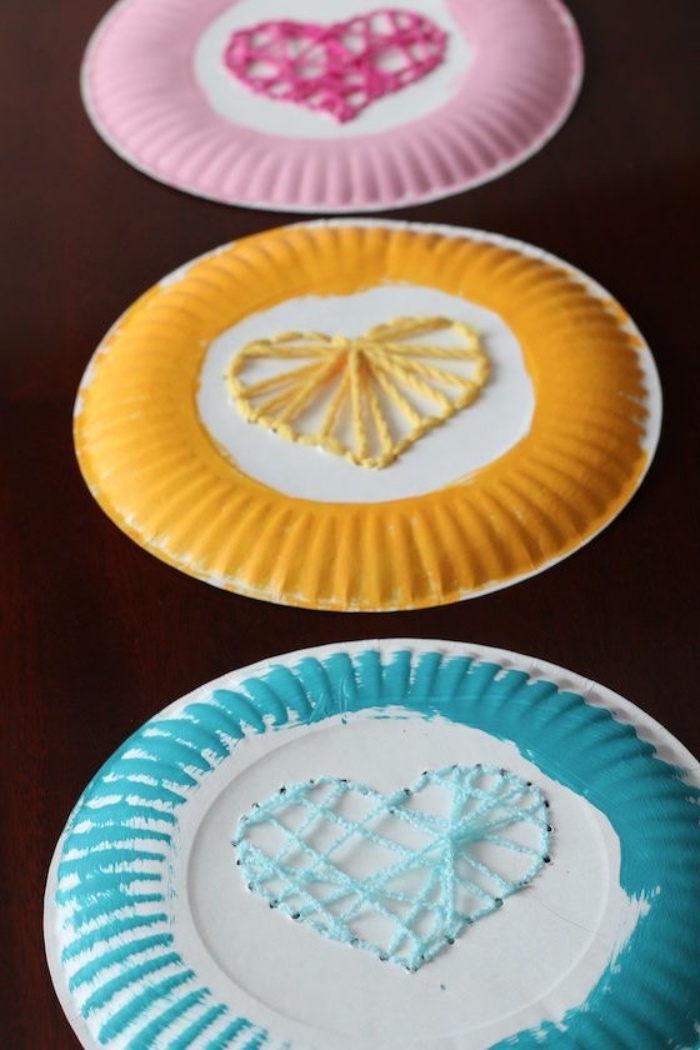 preschool classroom games, paper plates, painted in pink, yellow and blue, hearts made of strands