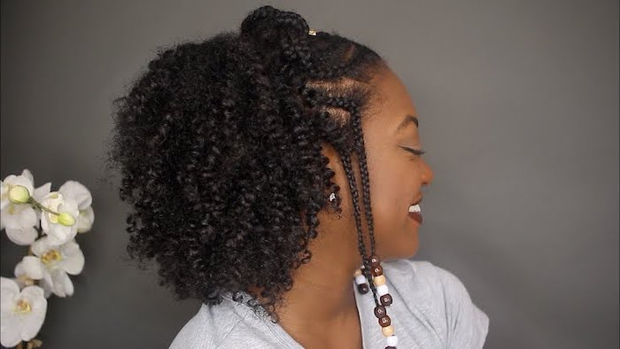 woman smiling, half up, half down hair, with beads, side braids with weave, wearing a grey t shirt