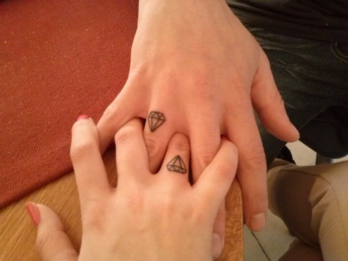 his and hers matching tattoos, diamond on the finger, intertwined fingers, wooden table