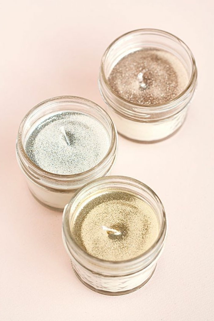 three small glass jars, glitter candle wax inside, how to make scented candles, pink background