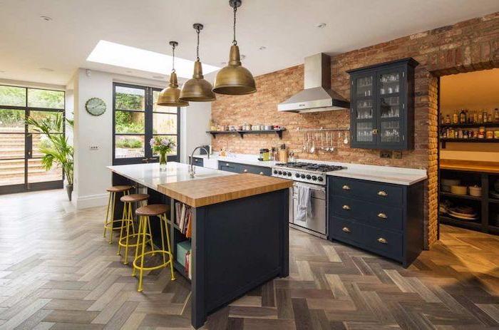 brick wall, grey cabinets and drawers, white countertops, kitchen island with bar seating, yellow metal bar stools