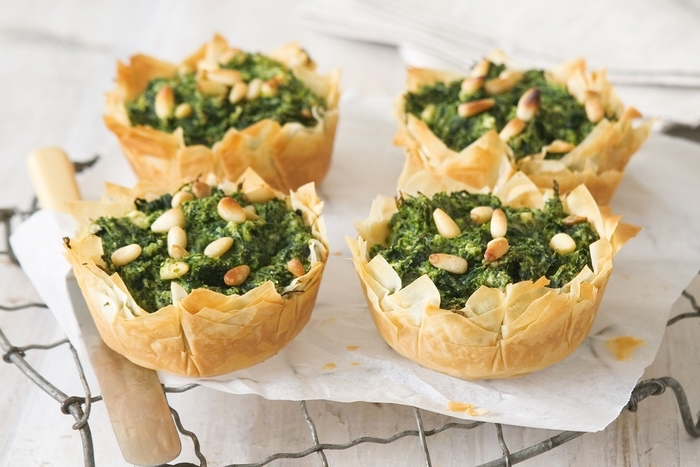bread bowls, filled with spinach and nuts, vegetarian finger food, on a metal stand