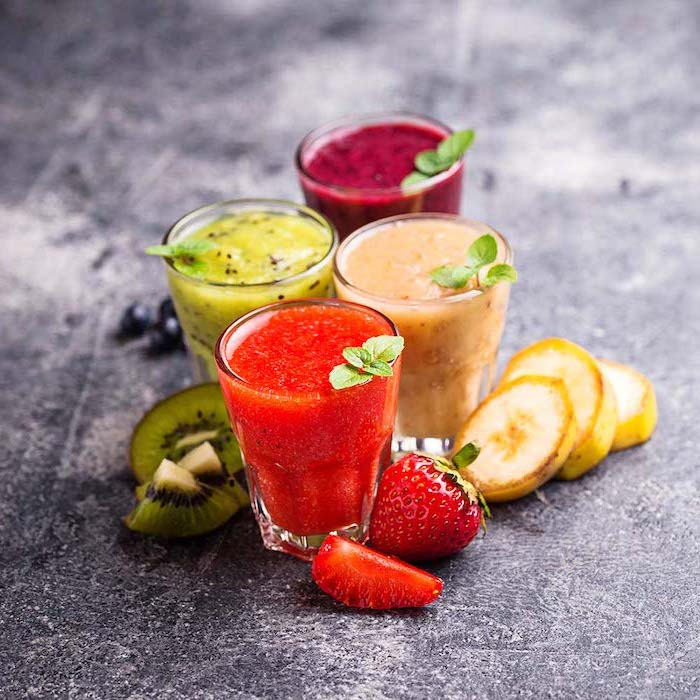 different smoothies, sliced kiwis and strawberries, healthy breakfast smoothie recipes, mint on top
