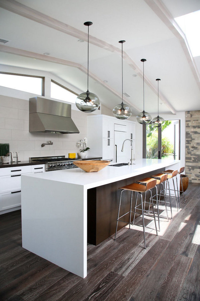 white tiled backsplash, wooden bar stools, white countertops, wooden floor, kitchen island with bar seating