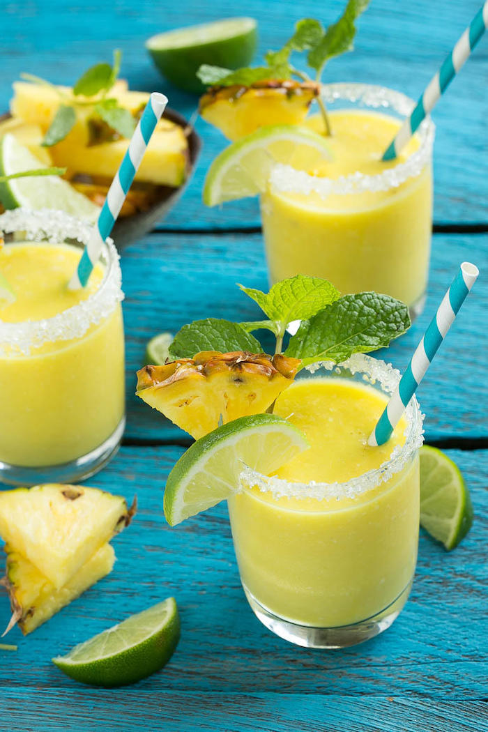 sugar on the rim, lime and pineapple slices, healthy breakfast smoothie recipes, mint on top, blue wooden table