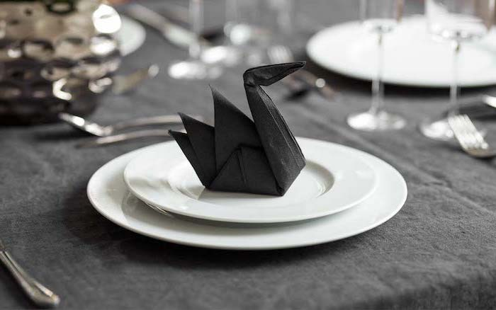 napkin folding ideas, black napkin, in the shape of a swan, on white plates