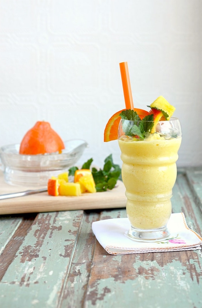 peanut butter and banana smoothie, tall glass, grapefruit slices on the rim, mint on top