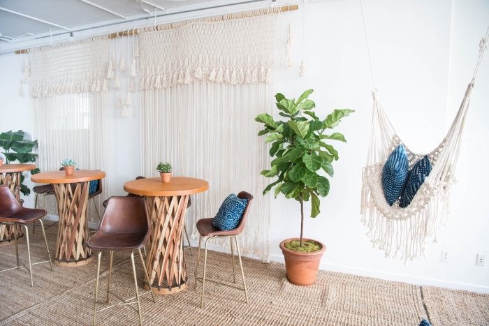 tall wooden tables, metal bar stools, white walls, macrame tapestry, macrame curtains, macrame hammock