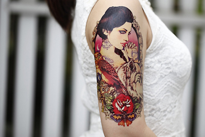 woman wearing a white top, meaningful tattoos, woman with wolf and bird, lots of flowers, shoulder tattoo