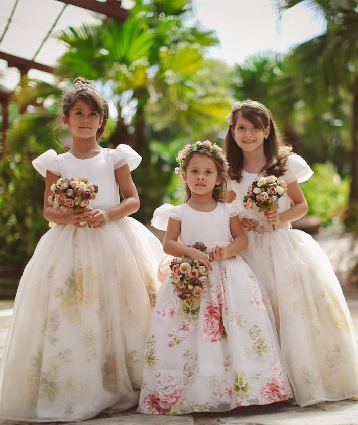 little girl dresses, three girls, with floral tulle dresses, brown hair, flower bouquets, greenery in the background