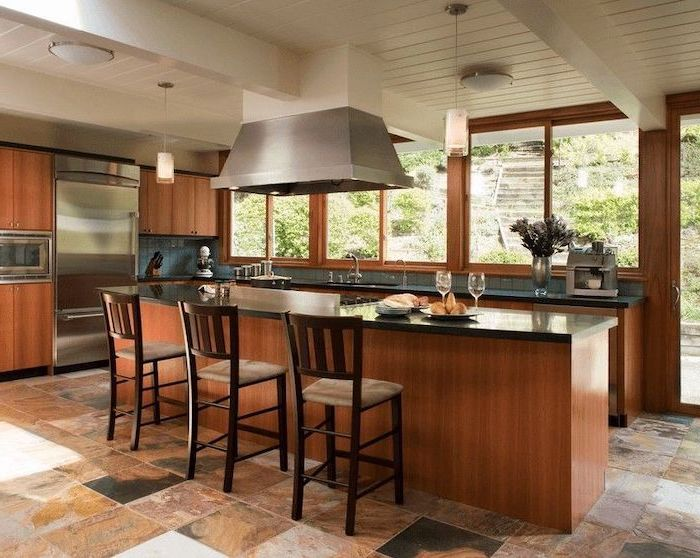 wooden bar stools, wooden cabinets, tiled floor, floating kitchen island, blue backsplash