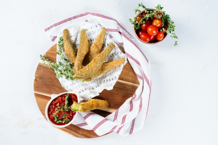avocado fries recipe, inside wooden bowl, tomato sauce and cherry tomatoes in small bowls