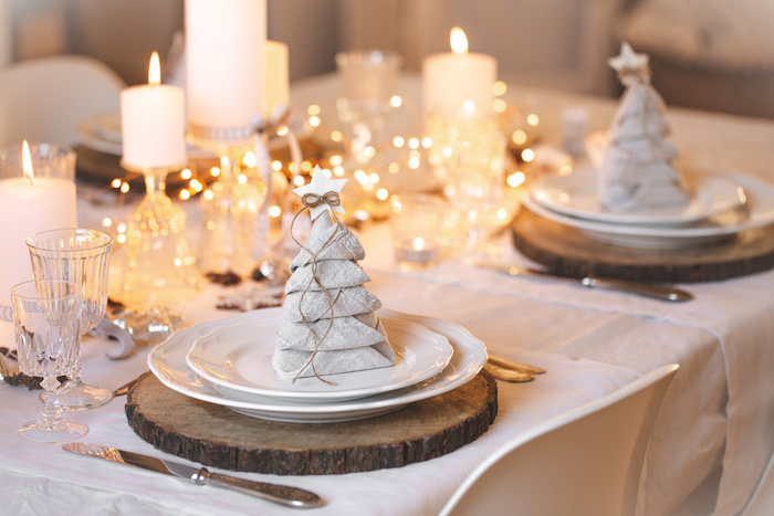 christmas tree shaped white napkins, on white plates, wooden boards, napkin folding ideas, candles and lights