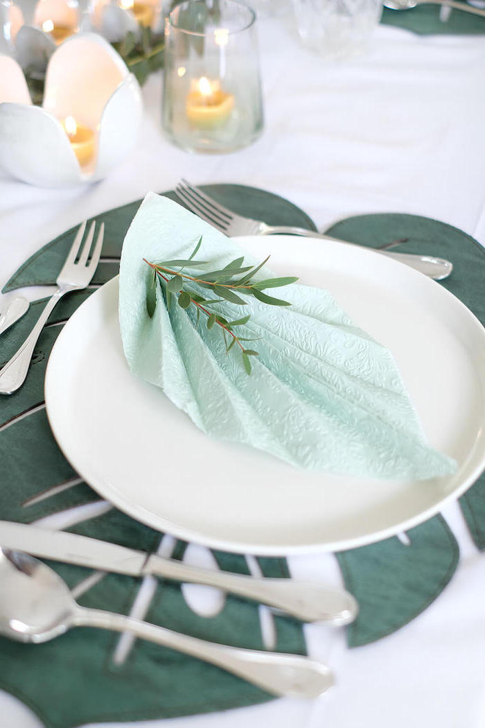 blue napkin, fan shaped, on a white plate, how to fold napkins with rings, silverware arranged