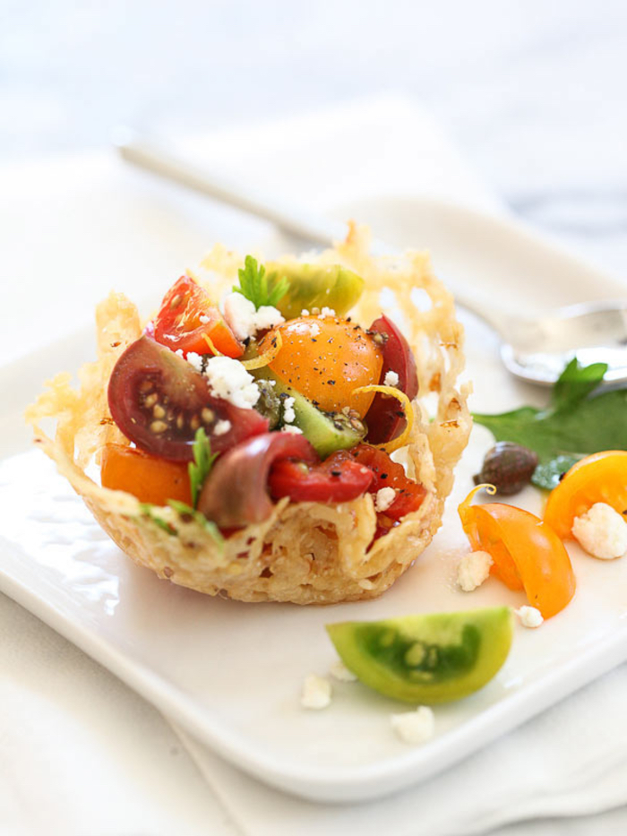 vegetarian appetizers, bread bowl, salad inside, made of red and orange cherry tomatoes