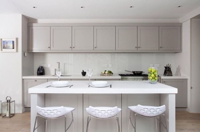 white bar stools, grey cabinets, white backsplash, wooden floor, floating kitchen island