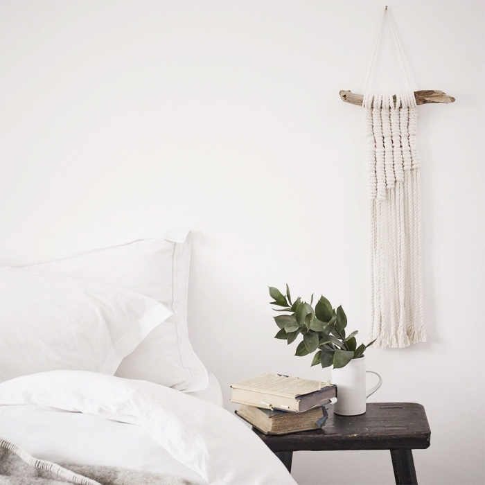 wooden night table, two books, ceramic pot, white bed linen, macrame tapestry