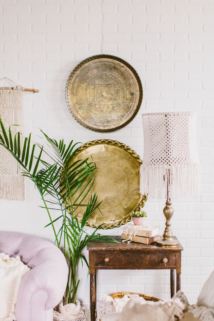 white brick wall, macrame tapestry, light purple sofa, potted palm tree, vintage wall decoration