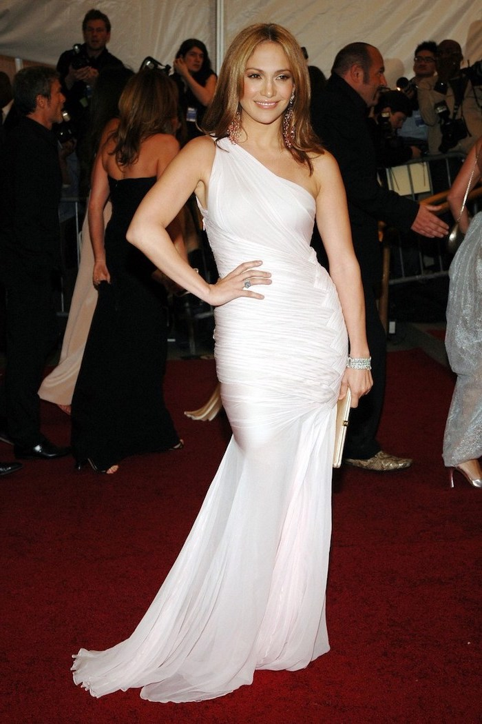white dress, jennifer lopez, on the red carpet, met gala fashion, long brown hair, white clutch bag