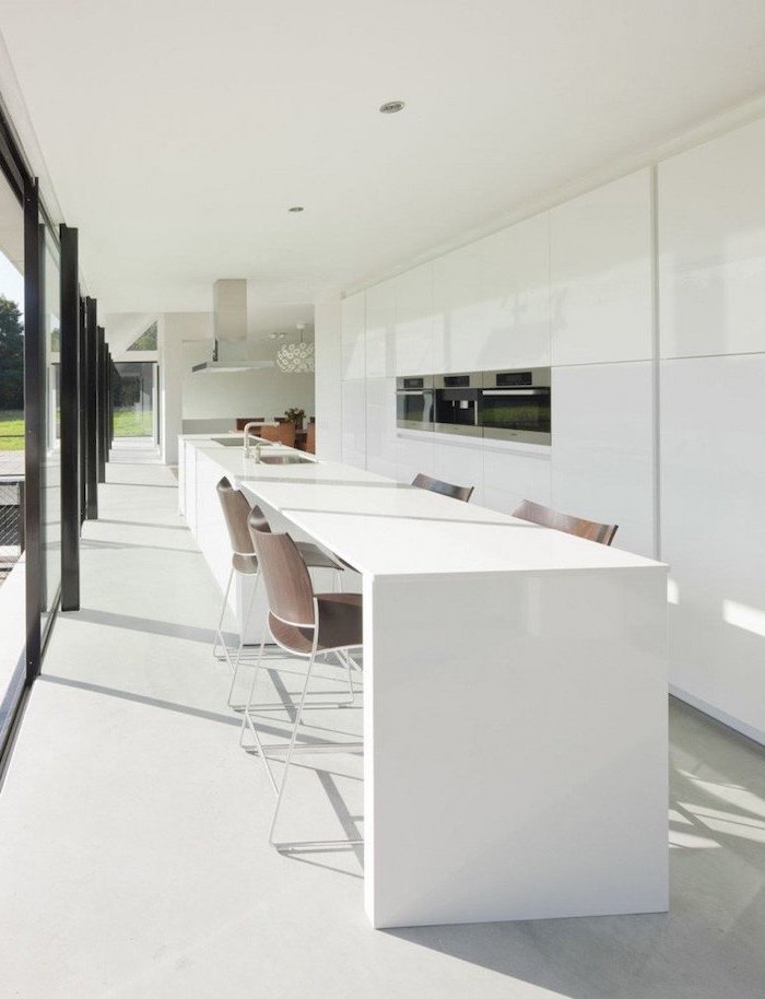 long white kitchen island, wooden chairs, how to make a kitchen island, white cabinets, large windows