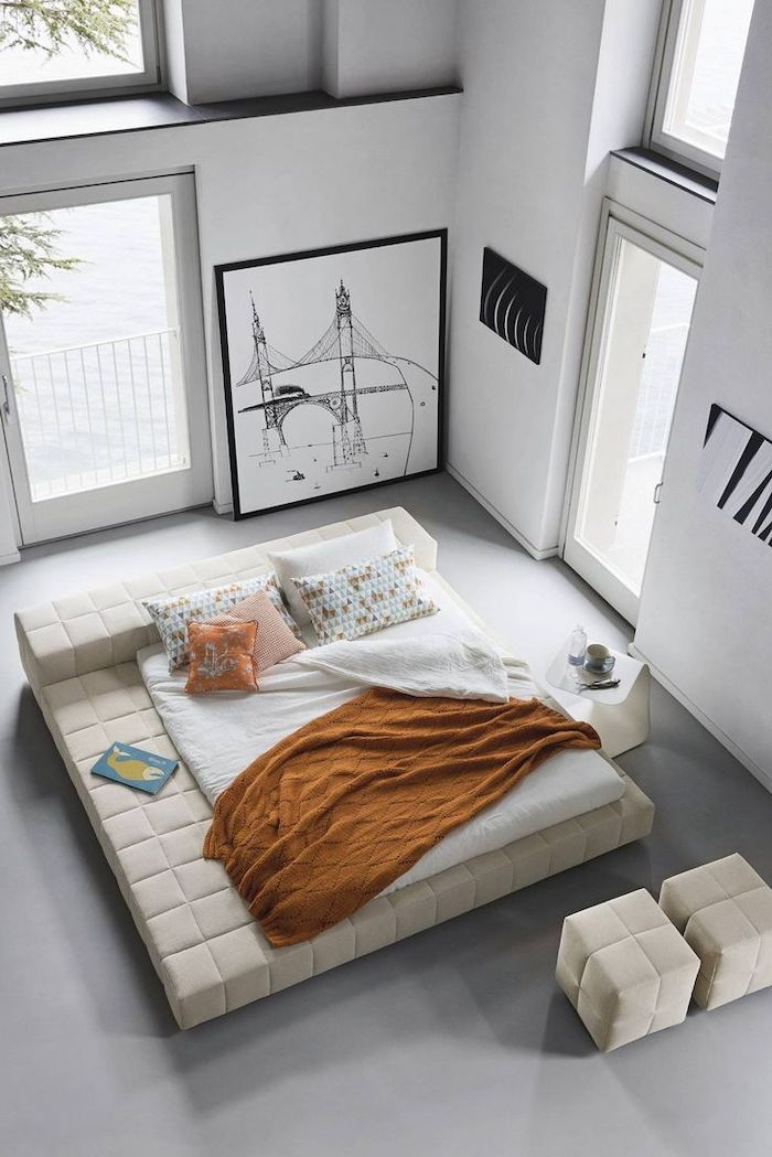white leather bed, master bedroom ideas, white leather ottomans, white walls, framed art