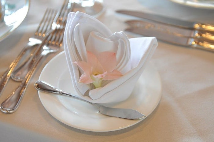 white napkin, flower shaped, pink flower inside, how to fold napkins with rings, on a white plate
