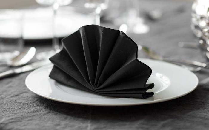 fan shaped, black napkin, napkin folding with silverware, on a white plate, black table cloth