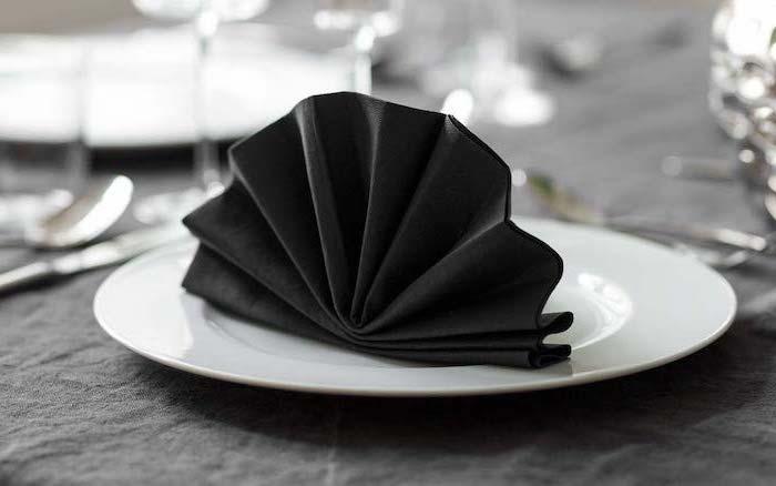 fan shaped, black napkin, napkin folding with silverware, on a white plate, black table cloth
