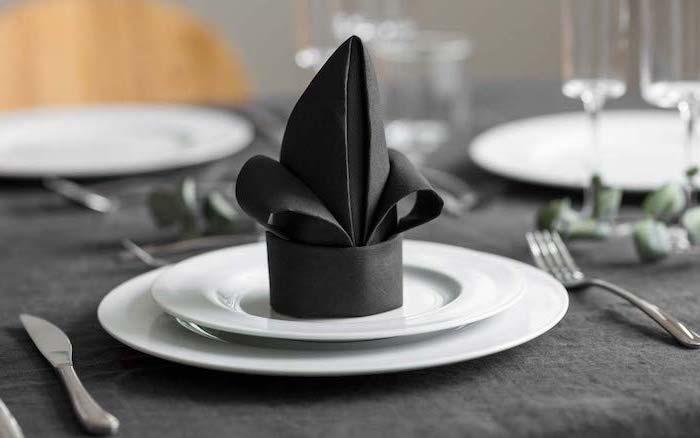 black napkin, on white plates, black table cloth, napkin folding with silverware, silverware arranged around it