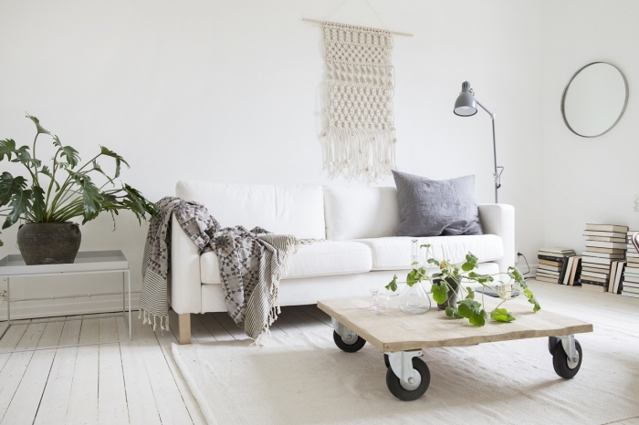 wooden table on wheels, white sofa, macrame wall hanging patterns free, grey blanket, potted plants