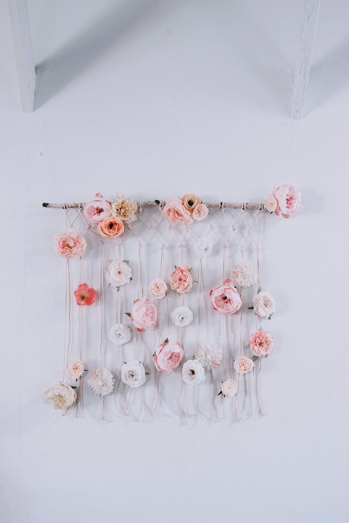 macrame wall hanging tutorial, intertwined with pink and white flowers, white wall