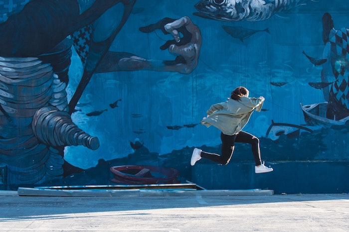 wall covered in blue graffiti, woman running, wearing white sneakers black pants, grey jacket