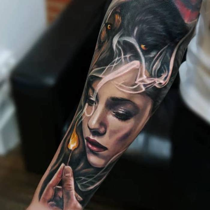 woman with a wolf head, holding a lit match, forearm tattoo, meaningful tattoos