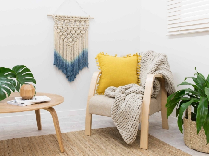 wooden armchair, knitted grey blanket, woven wall hanging, wooden table, potted plants, white walls