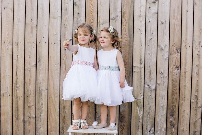 two girls, standing on a white table, wooden background, flower girl shoes, floral ribbon, blonde hair