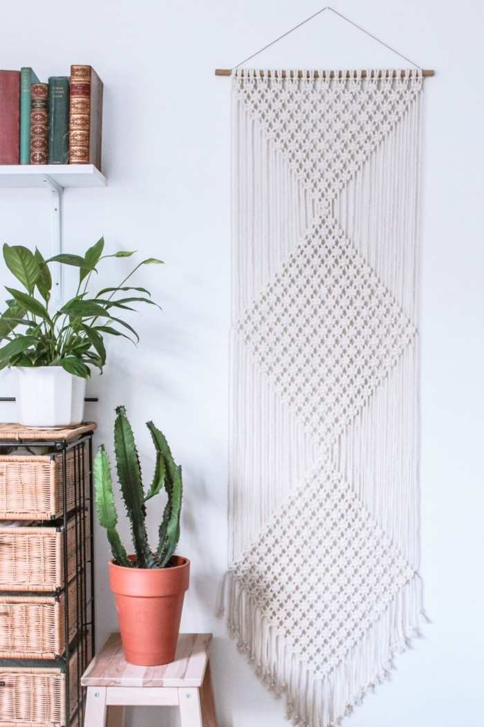wooden bookshelves and drawers, potted cactus, white wall, woven tapestry wall hanging, small wooden chair