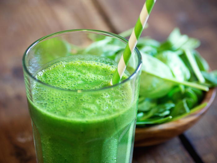spinach in a wooden bowl, how to make a green smoothie, green and white paper straw