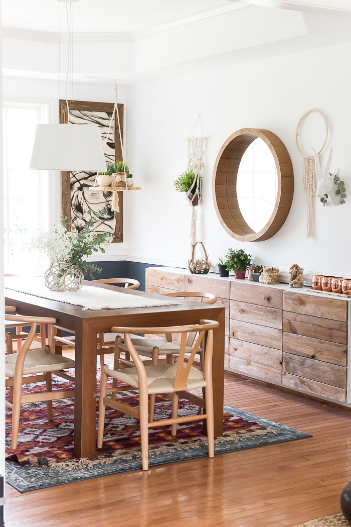 round wooden mirror frame, wooden floor, macrame backdrop, wooden chairs and table, printed rug