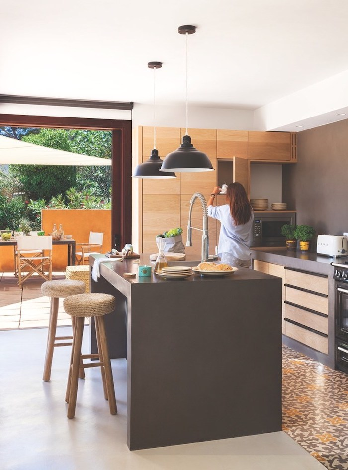 wooden cabinets, black countertops, tiled floor, wooden bar stools, pictures of kitchen islands, white floor