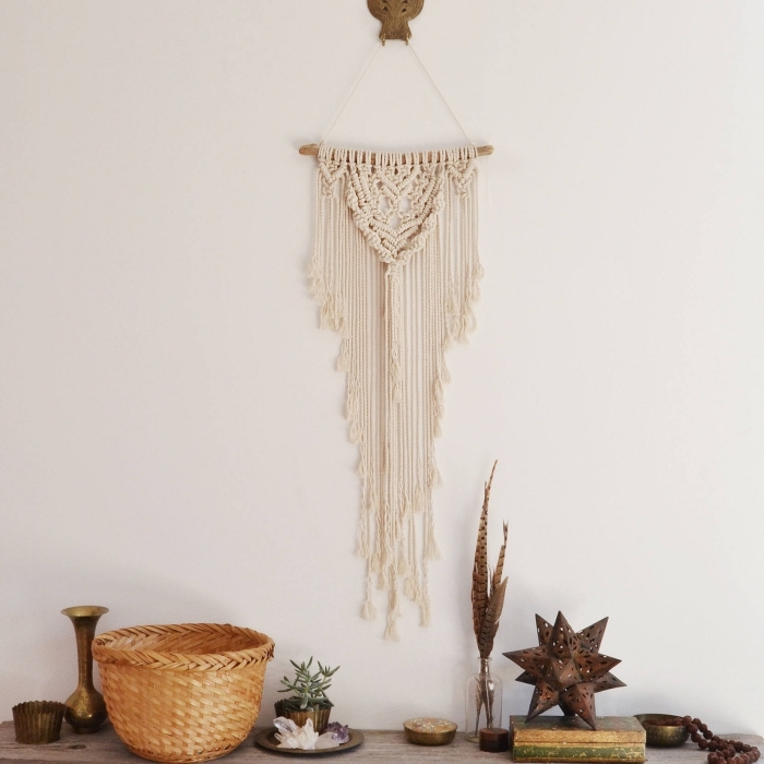 white wall, wooden basket, wooden table, macrame wall hanging knots, metal vase, potted succulent