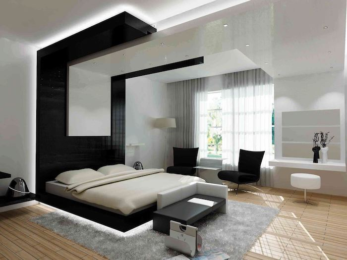 black and white tiled accent wall, wooden floor, grey carpet, how to decorate room, black armchairs