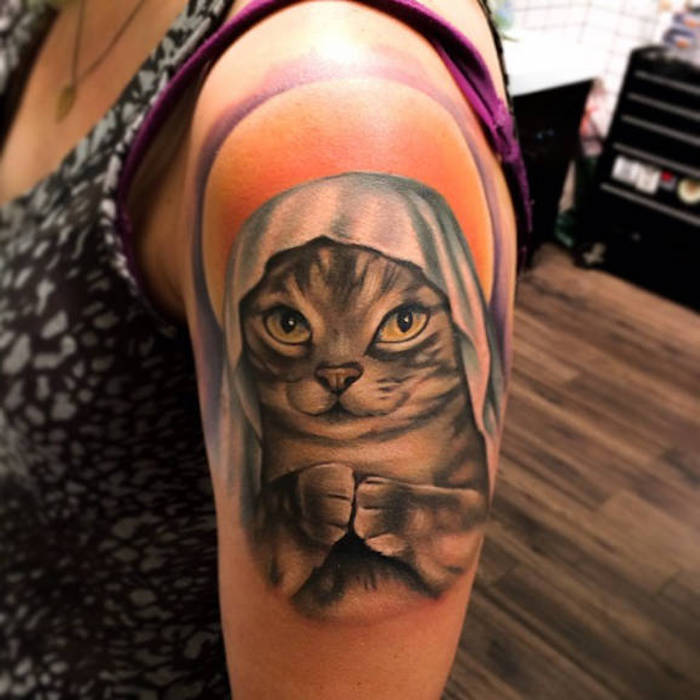 cat head, tattoos for women, shoulder tattoo, black and grey top, wooden floor